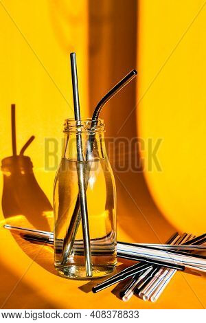Stainless Steel Reusable Drinking Straw With Many Multicolored Plastic Straws On Yellow Background.