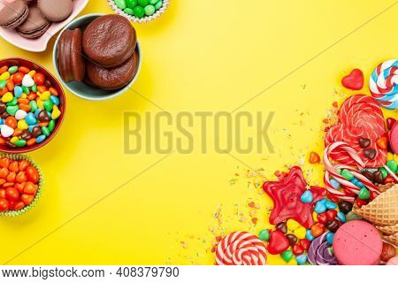 Various sweets assortment. Candy, bonbon and macaroons on yellow background. Top view flat lay with copy space