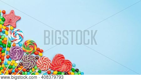 Various sweets assortment. Candy, bonbon and lollipop on blue background. Top view flat lay with copy space