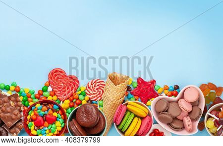 Various sweets assortment. Candy, bonbon, chocolate and macaroons over blue background. Top view flat lay with copy space