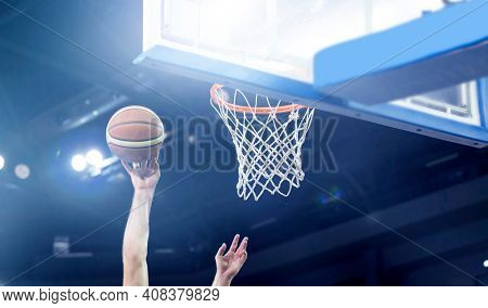 Ball in hoop at basketball game. Athletic competitions and games concept.
