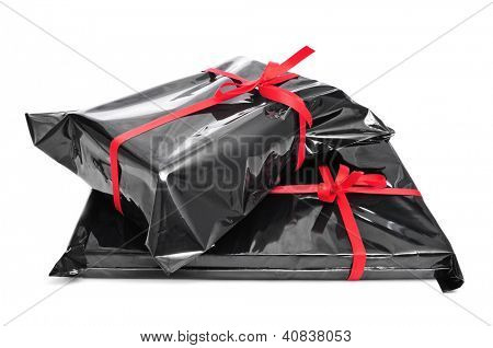 a pile of gifts wrapped with black plastic and tied with red ribbons on a white background