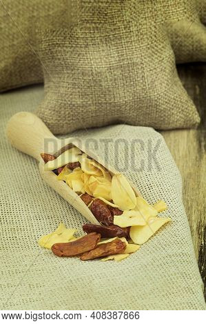 Spices On A Wooden Spoon On A Wooden Background With Copy Space. Dried Garlic And Chili Peppers On A