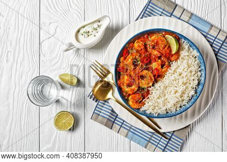 Tomato Prawn Curry With Coriander Sprouts And Red Chili On Top Served On A Plate With Jasmine Rice A