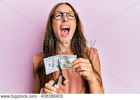 Young brunette woman cutting dollars with scissors for currency devaluation angry and mad screaming frustrated and furious, shouting with anger looking up.