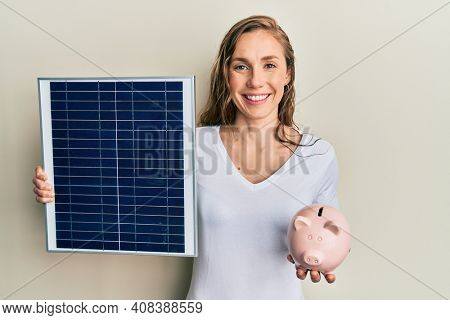 Young blonde woman holding photovoltaic solar panel and piggy bank smiling with a happy and cool smile on face. showing teeth.