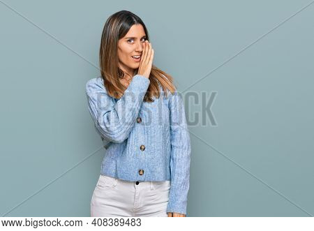 Young woman wearing casual clothes hand on mouth telling secret rumor, whispering malicious talk conversation