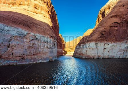 Grandiose cliffs - red sandstone outcroppings. Tour on a pleasure boat on an artificial reservoir Lake Powell. The Colorado River and Antelope Canyon. Concept of active and photo tourism