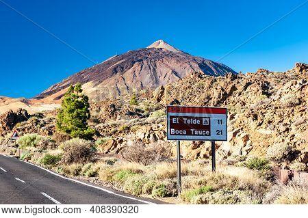 Silhouette Of Volcano Del Teide And Signpost Against  Blue Sky. Pico Del Teide Mountain In El Teide