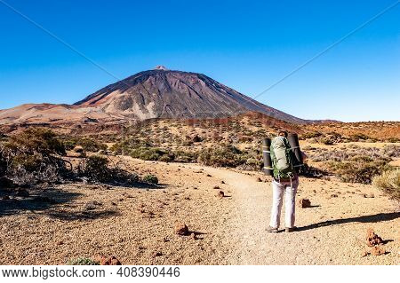 Young Woman Hiker With Backpack Looking At Pico Del Teide Mountain In El Teide National Park. Teneri