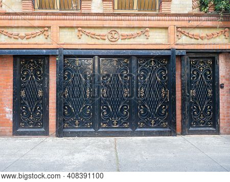 Black Iron Garage Gates And Doors With An Elaborate Gilded Pattern Of Monograms And Bars In A Brick