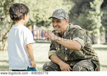 Happy Military Father Meeting With Son After Mission Trip. Boy Walking To Dad Wearing Camouflage Uni