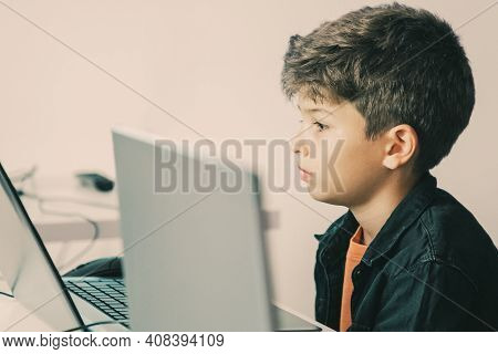 Serious Pupil Sitting At Table And Looking At Laptop Screen. Concentrated School Boyreading Task Or