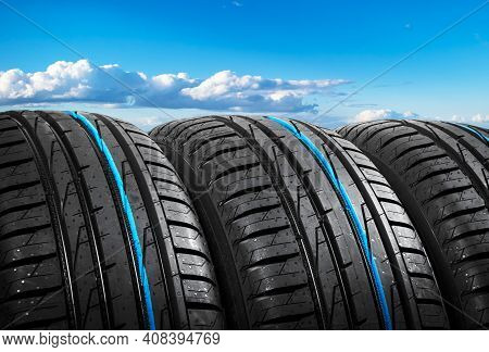 Summer Car Tires On Over Blue Sky With Clouds. Tire Stack Background. Car Tyre Protector Close Up. B
