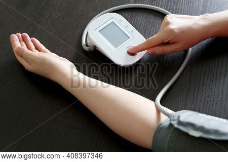 Woman Measuring The Pressure With Blood Pressure Monitor, Selective Focus On Right Female Arm. Healt