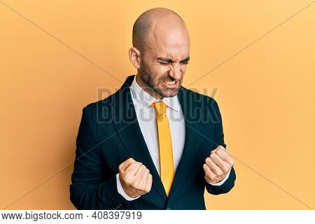 Young hispanic man wearing business suit and tie very happy and excited doing winner gesture with arms raised, smiling and screaming for success. celebration concept.