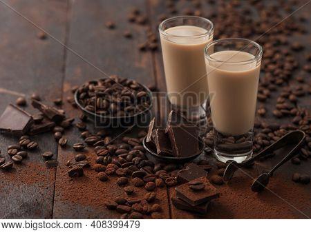 Shot Glasses Of Irish Cream Baileys Liqueur With Coffee Beans And Powder With Dark Chocolate On Dark