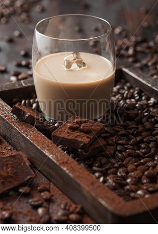 Glass With Ice Cubes Of Irish Cream Baileys Liqueur In Wooden Tray With Coffee Beans And Powder With
