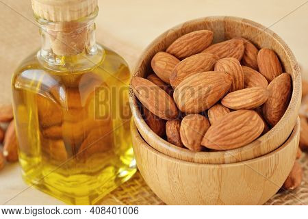 Bottle Of Almond Oil And Almonds In Wooden Bowl