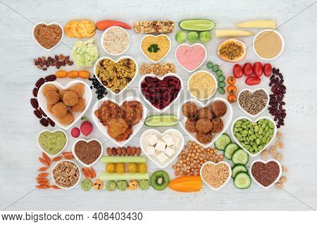 Vegan health food for a plant based diet with foods high in antioxidants, protein, minerals, fibre, omega 3, anthocyanins, vitamins, and smart carbs. Flat lay on rustic wood. Ethical eating concept.