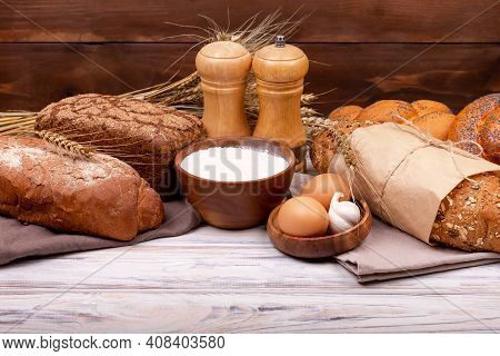 Collection Of Grain Bread And Baked Goods On Wooden Background. Various Bread Rolls. Healthy Bread A