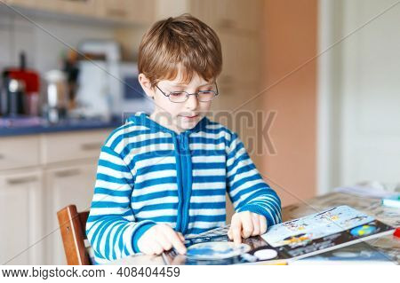 Adorable Little Kid Boy With Glasses Reading Book. Cute Happy School Child And Student Learning Lett