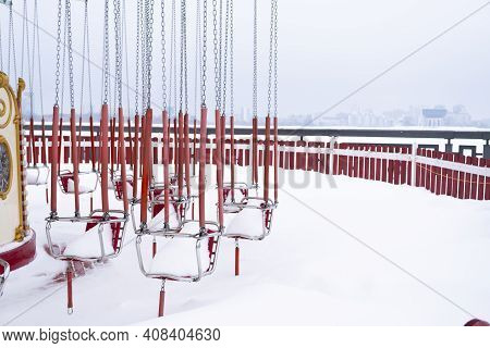 Carousel In Winter. Snow-covered Swing. Abandoned Carousel