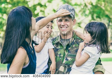 Joyful Military Father In Uniform Returning To Family, Holding Two Kids In Arms. Woman Adjusting Hus