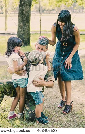 Happy Mother And Two Children Hugging Military Father In Camouflage Uniform Outdoors. Vertical Shot.