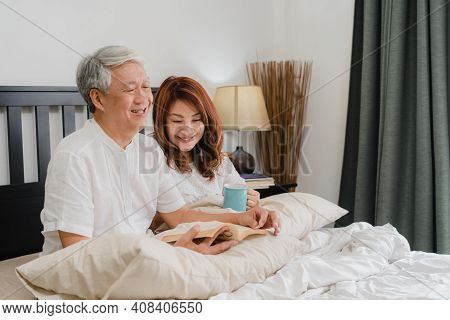 Asian Senior Couple Talking On Bed At Home. Asian Senior Chinese Grandparents, Husband And Wife Happ