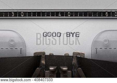 Typing text GOOD BYE on vintage manual typewriter. Close up of writes word on white paper. Shot in macro.