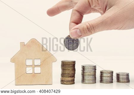The Hand Adds A Coin To The Pile, There Is A House Nearby. Toning. The Concept Is The Accumulation O