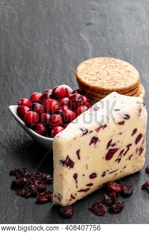 Cranberry  Cheddar Cheese With Fresh Cranberry On Black Stone Background
