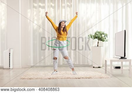 Full length portrait of a young woman spinning a hula hoop at home in a living room