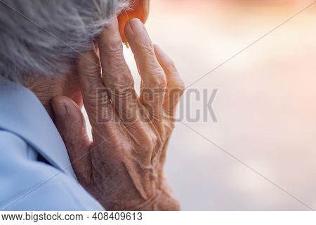 Back View Of Elderly Woman Hand Touch In The Ear Her. Focus On Hands Wrinkled Skin. Space For Text.