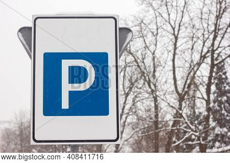 Parking Sign On The Background Of Sky And Trees In Winter Autumn Time Close Up