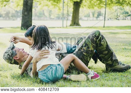 Joyful Kids And Their Dad Lying And Playing On Grass In Park. Happy Military Father Meeting With Chi