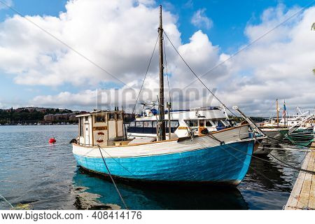 Stockholm, Sweden - August 9, 2019: Old Blue Fishing Boat Moored In The Harbour