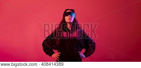 Young Girl Wearing Galactic Glasses Looking At Camera With Her Hands On The Hips, Against Red Backgr