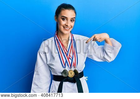 Beautiful brunette young woman wearing karate fighter uniform and medals pointing finger to one self smiling happy and proud
