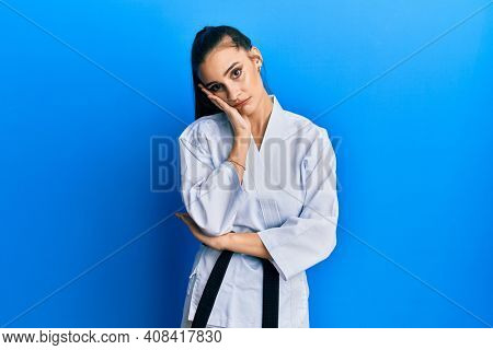 Beautiful brunette young woman wearing karate fighter uniform with black belt thinking looking tired and bored with depression problems with crossed arms.
