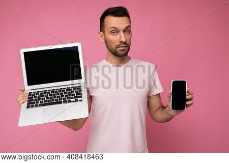 Handsome Amazed Brunet Man Holding Laptop Computer And Mobile Phone Looking At Camera In T-shirt On
