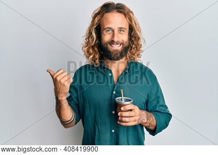 Handsome man with beard and long hair drinking mate infusion pointing thumb up to the side smiling happy with open mouth