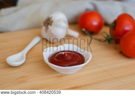 Ketchup Or Tomato Sauce In A Bowl, Whole Tomatoes, Garlic Close-up. Background With Ketchup, Tomatoe