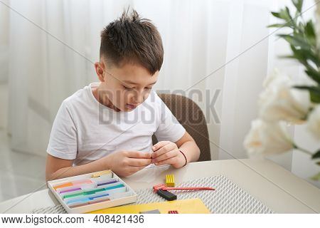 Boy Sculpts Figures From Plasticine, Sitting At Home At The Table. He Is Passionate About His Hobby