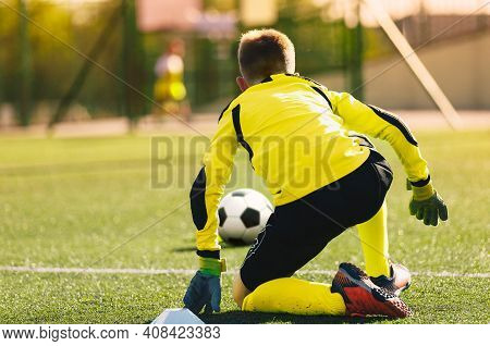 Young Soccer Goalie In Action. Boy Soccer Player Ready To Catch Ball And Safe Goal. Kid Goalkeeper I