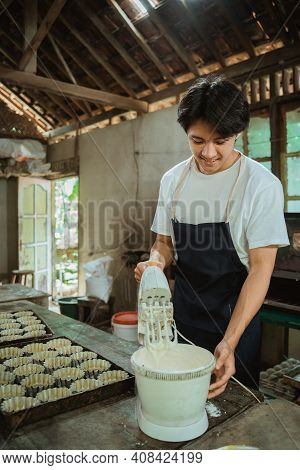 A Man Being Concentrated Using A Hand Mixer Up Some Cookie Batter Beside Baking Sheet Cake