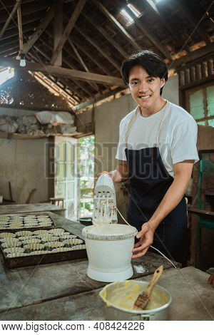 Smiling Young Man Using A Hand Mixer Up Some Cookie Batter Beside Baking Sheet Cake