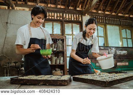 A Man In An Apron Pours The Cake Batter Into The Mold And A Woman Stirs The Dough Near The Cake Tin