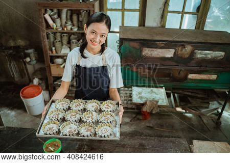A Woman Wearing A Smiling Apron Carries A Baking Sheet Of Several Cookie Cutters